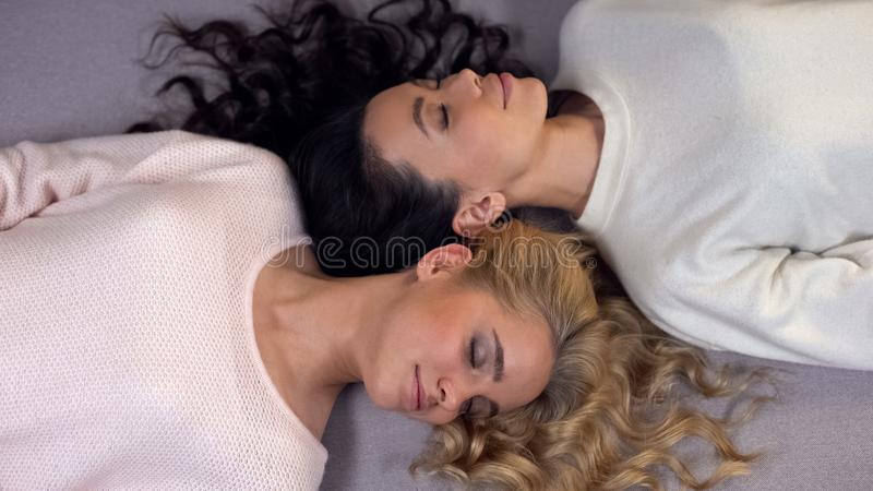 Привлекательные блондинка и брюнет с глазами закрыли лежать на поле, представляя на камере стоковое изображение