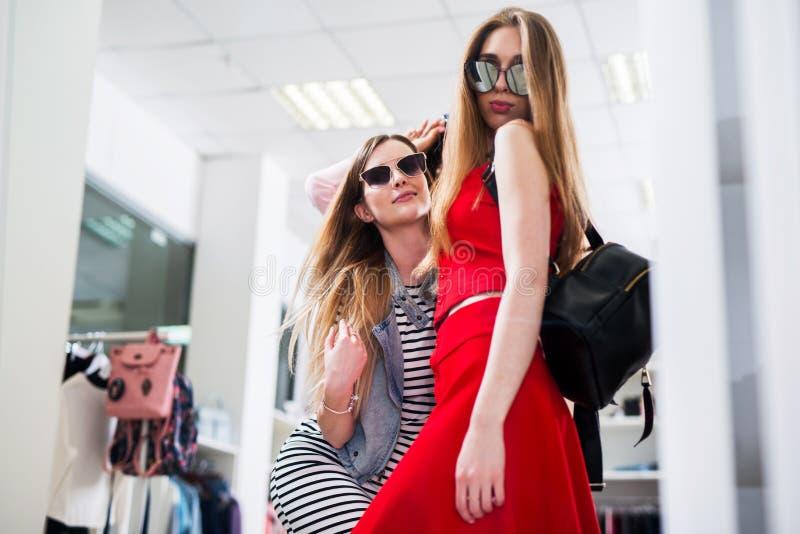 Привлекательные женские модели рекламируя новое собрание солнечных очков лета в магазине моды стоковые изображения rf