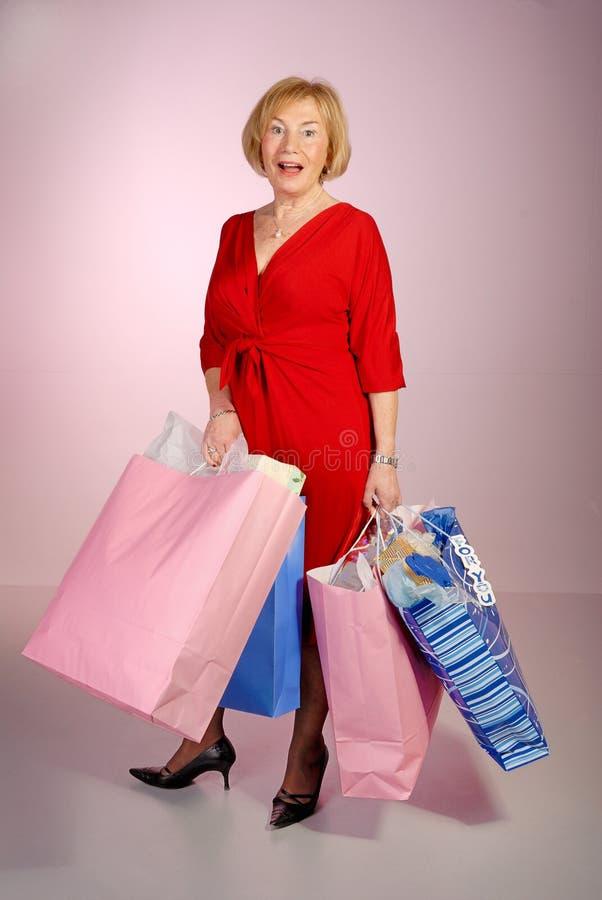привлекательные мешки держа покупку повелительницы более старую стоковые фото