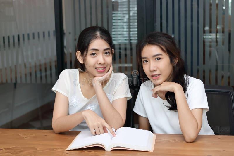 Привлекательные молодые азиатские женщины при книга смотря камеру в живущей комнате стоковые изображения rf