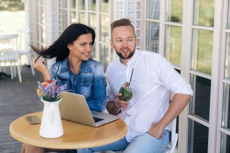 Привлекательные молодые парни сидят на таблице на террасе в кафе, наслаждаются напитками, беседой на темах потехи Фрилансер парня стоковое изображение