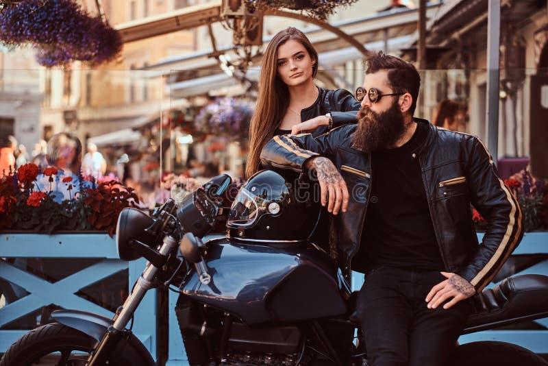 Привлекательные пары битника - бородатый зверский мужчина в солнечных очках одел в черной кожаной куртке и его детенышах чувствен стоковая фотография rf