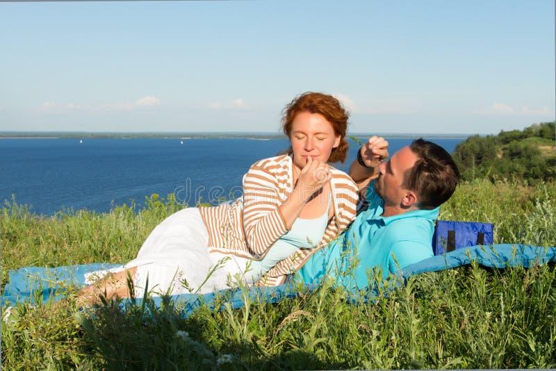 Привлекательные пары имеют остатки в траве близко большого озера Любящие пары в летнем дне счастливые лежа пары стоковое изображение