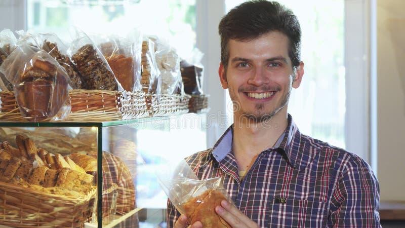 Привлекательные печенья молодого человека покупая на хлебопекарне стоковое фото rf