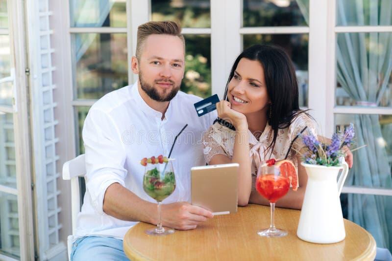 Привлекательные счастливые сияющие любовники имеют европейское возникновение, сидят на таблице в кафе, используют планшет, делают стоковое изображение