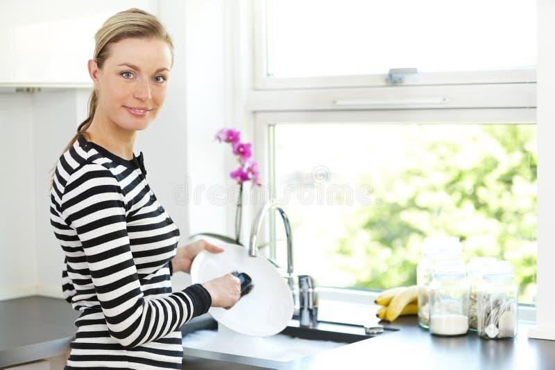 Привлекательные тарелки чистки женщины стоковое фото