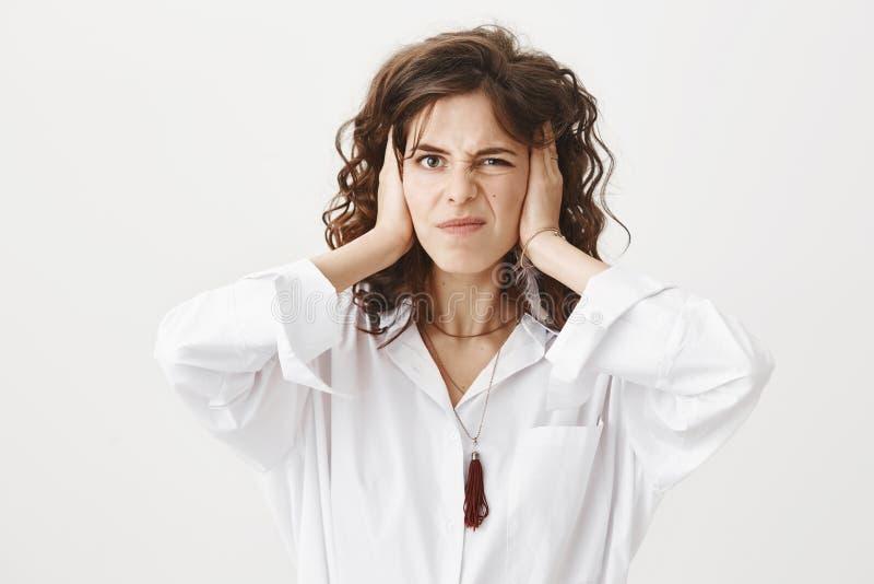 Привлекательные уши заволакивания взрослой женщины при руки и annoyens и нелюбовь выражать, жмурясь от ужасного звука стоковое изображение