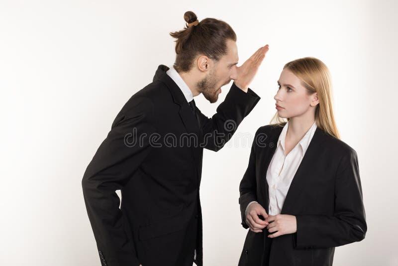 Привлекательный бизнесмен с бородой и ультрамодный стиль причесок в черном костюме кричащем на его подчиненном который не может с стоковые изображения rf