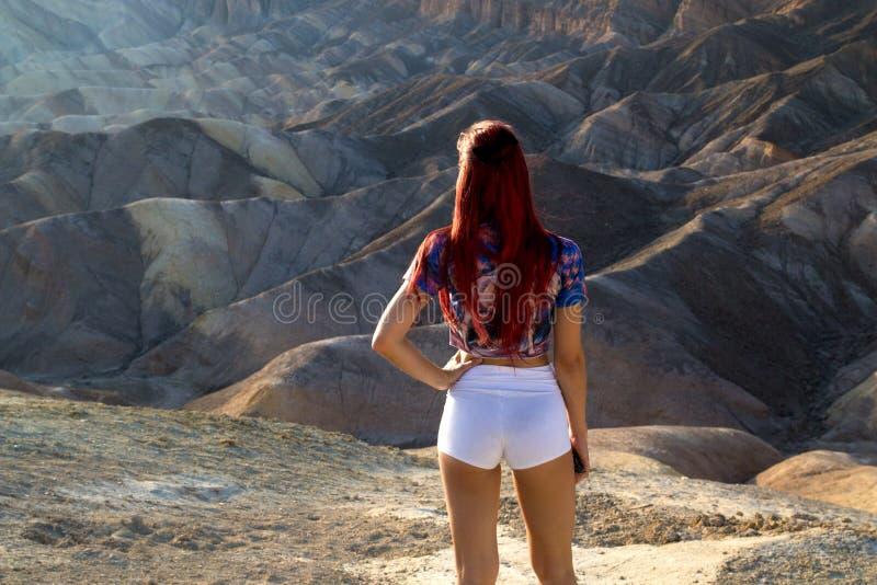 Привлекательный взгляд задней части молодой женщины стоя перед сногсшибательным старым ландшафтом пустыни, самым горячим местом в стоковое изображение rf