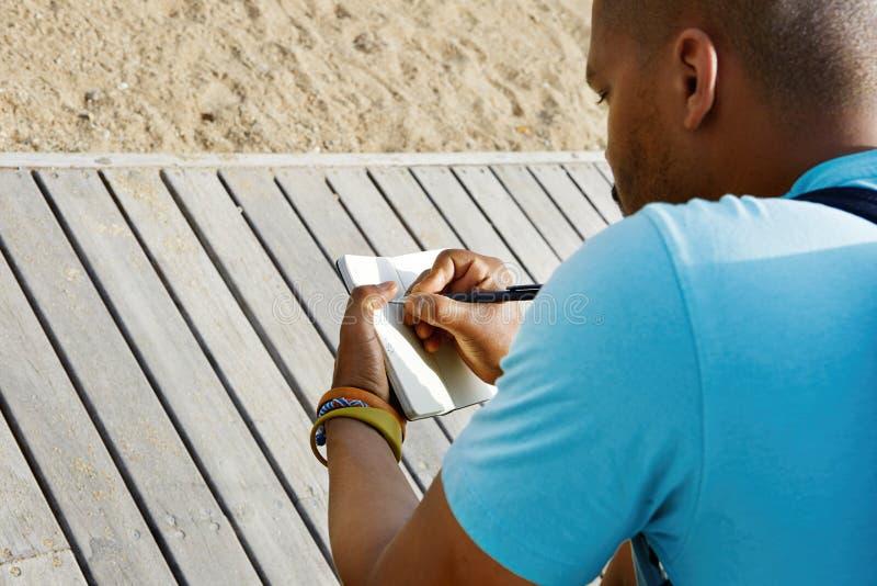 Привлекательный вскользь одетый молодой американский африканский человек делая примечания в тетради с прописями Студент подготавл стоковое фото rf