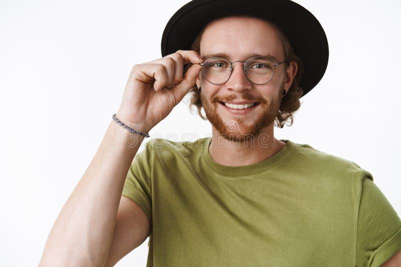 Привлекательный выглядящий дружелюбн харизматический молодой бородатый парень в стеклах и шляпе касаясь рамкам eyewear и усмехать стоковые фото