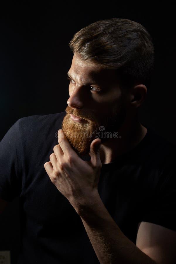 Привлекательный задумчивый молодой человек смотрит в расстояние штрихуя его бороду стоковая фотография