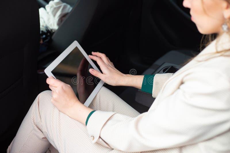 Привлекательный исполнительный женский менеджер работая с планшетом в заднем сиденье автомобиля стоковое фото