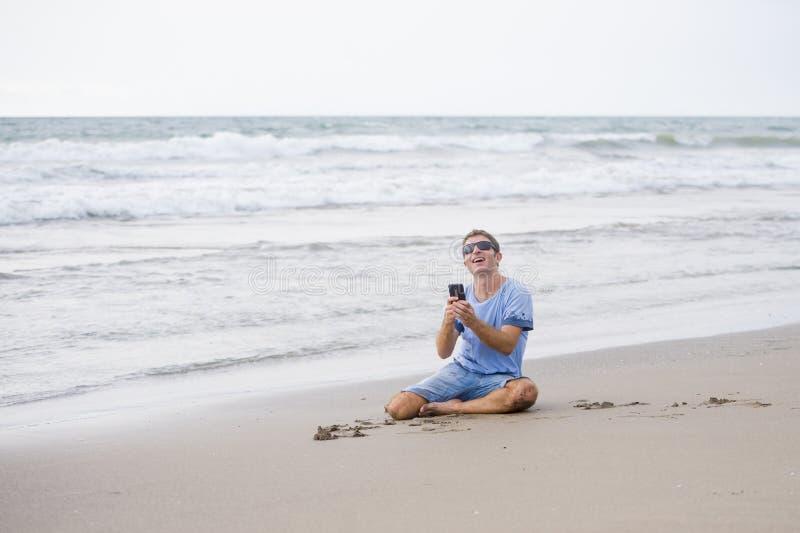 Привлекательный и красивый человек на его 30s сидя на песке ослабил на пляже смеясь над перед морем отправляя СМС на передвижном  стоковое фото