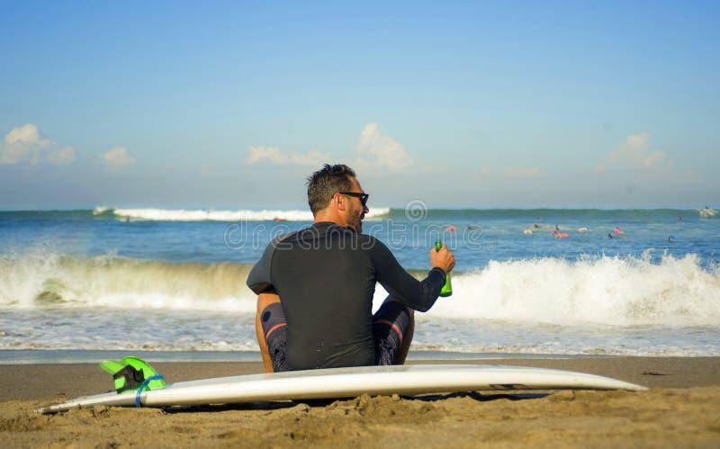 Привлекательный и счастливый человек 3os серфера к 40s в купальнике неопрена занимаясь серфингом представляя с доской прибоя сидя стоковые изображения rf