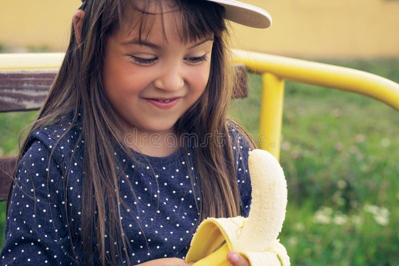 Привлекательный кавказский ребенок брюнет с длинными волосами, в голубой футболке и белой крышке есть банан и улыбки на пикнике стоковое изображение rf