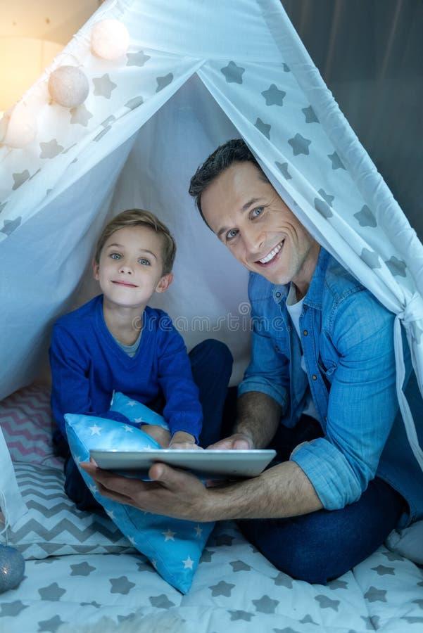 Привлекательный мальчик держа голубую подушку стоковая фотография rf