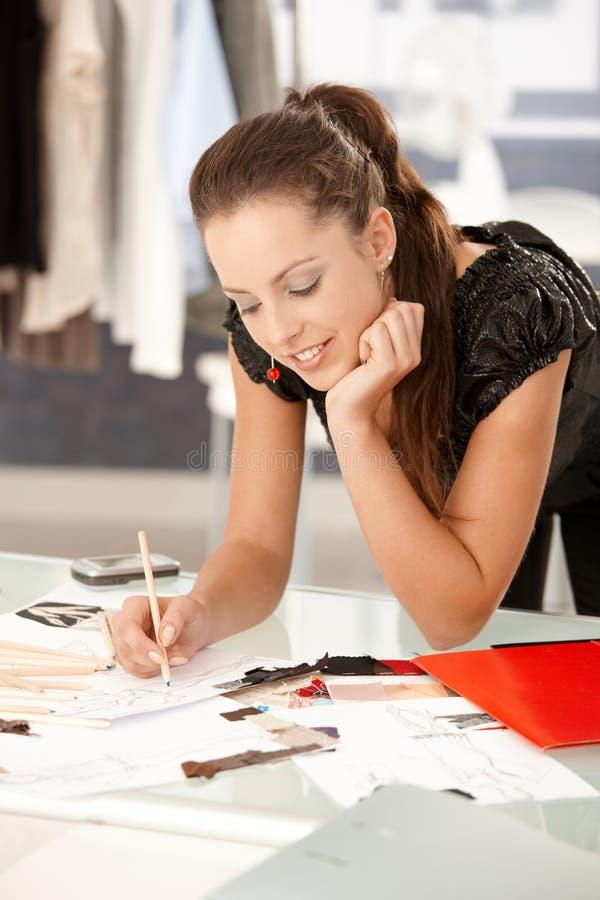 Привлекательный модельер работая в офисе стоковая фотография