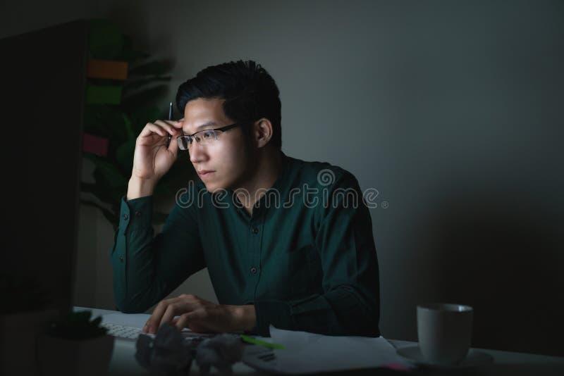 Привлекательный молодой азиатский человек сидя на таблице стола смотря ноутбук в темной ночной работая мысли чувства серьезной стоковое фото rf