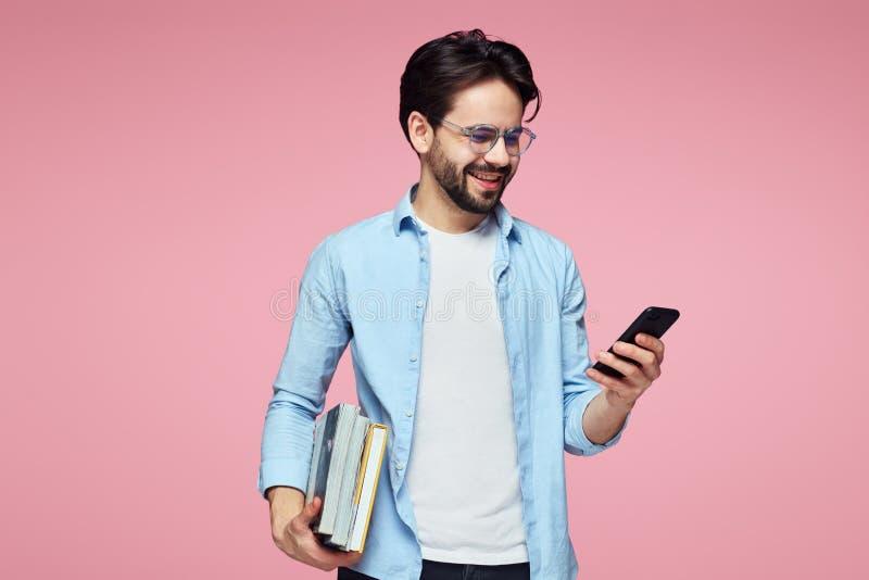 Привлекательный молодой бородатый студент держа книги и используя мобильный телефон пока стоящ над розовой предпосылкой стоковое изображение