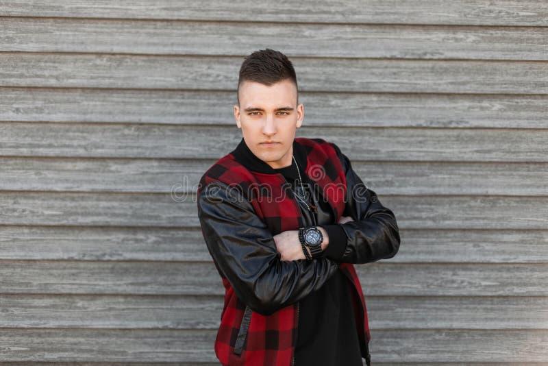 Привлекательный молодой человек в винтажной куртке шотландки со стильным стилем причесок в футболке с часами представляет около д стоковые изображения rf