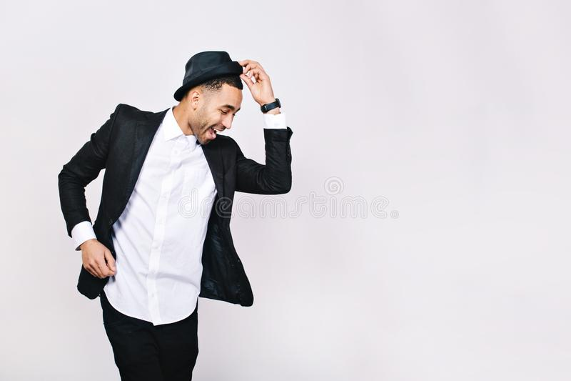 Привлекательный молодой человек в танцах костюма, имеющ потеху на белой предпосылке Стильный внешний вид, шляпа, успешный бизнесм стоковые фото