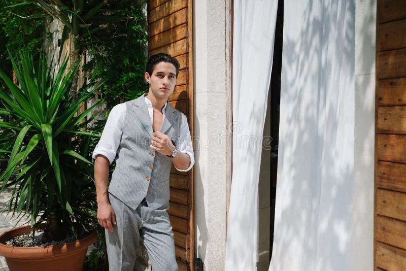 Привлекательный молодой человек моды в костюме идет вокруг старого городка стоковое изображение rf