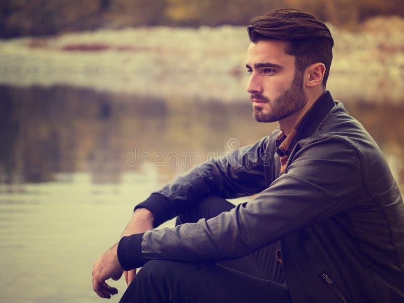 Привлекательный молодой человек на озере в солнечном стоковые фото