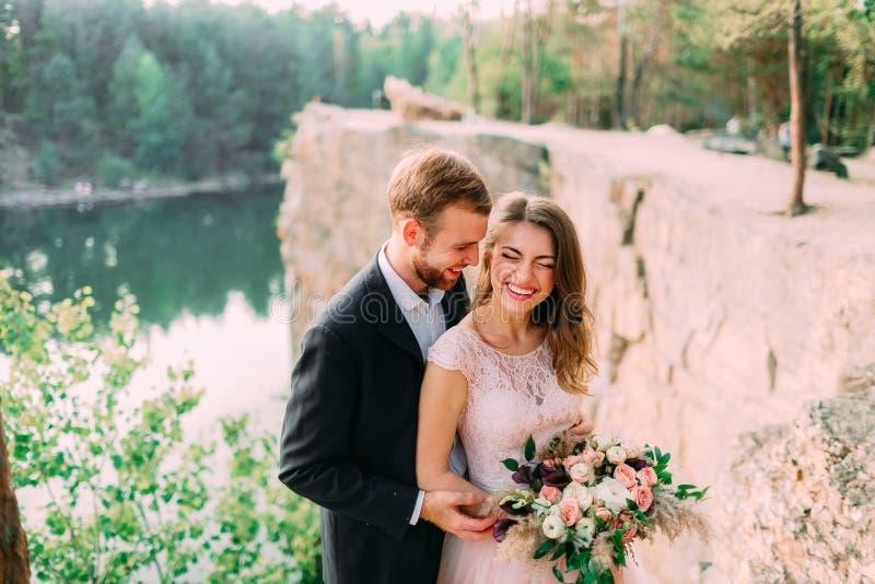 Привлекательный момент смеха и улыбки, счастливых и радостного жениха и невеста новобрачных пар церемония outdoors wedding стоковые фотографии rf