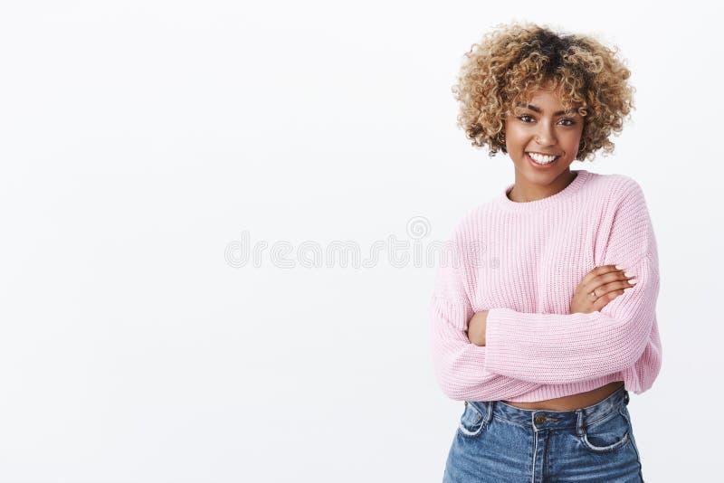 Привлекательный общительный и харизматический Афроамериканец женское 20s с курчавыми светлыми волосами в теплом удерживании свите стоковое изображение