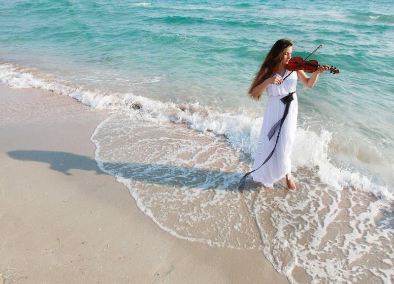 привлекательный пляж играя женщину скрипки стоковое фото rf