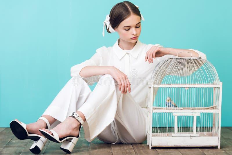 привлекательный подросток в белом обмундировании с попугаем в клетке стоковое фото rf