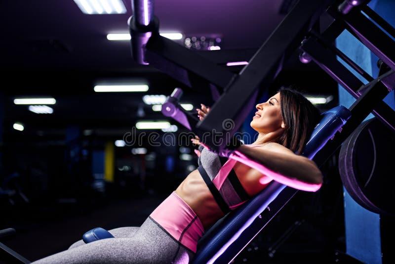 Привлекательный подходящий спортсмен женщины среднего возраста делая тренировки на pectoral мышцах в имитаторе Машина спортзала стоковые фото