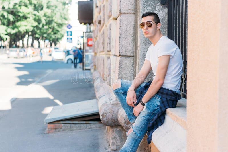 Привлекательный, сексуальный парень сидит на улице в солнечных очках самоуверенность, метеоризм и заносчивость модель, представля стоковые фото
