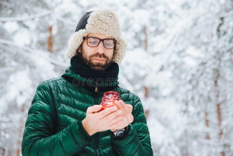Привлекательный серьезный мужчина носит теплые одежды зимы, держит свечу, стоит против предпосылки леса зимы, наслаждается свежим стоковое изображение rf