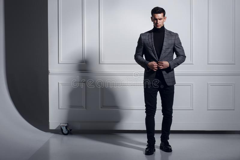 Привлекательный, сильный, мышечный молодой человек одел элегантно костюм представляя в студии, стоя около стены, предпосылка тене стоковые изображения