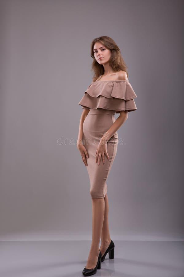 Привлекательный сказал женщину представляя в светлом платье на серой предпосылке стоковая фотография
