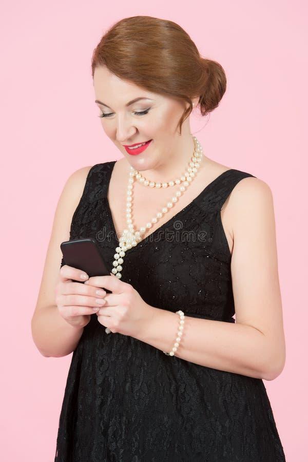 Привлекательный счастливый красный штырь-вверх волос ввел женщину в моду с красными губами и винтажными sms сочинительства состав стоковое фото rf