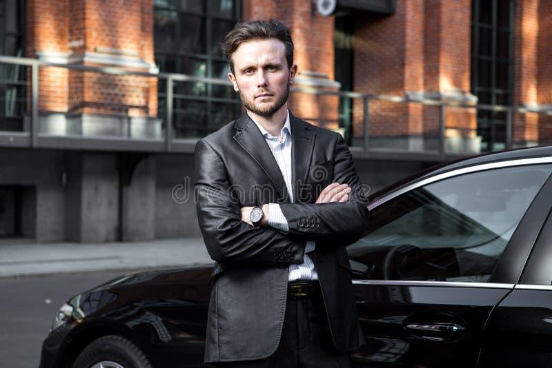 Привлекательный успешный молодой бизнесмен в деловом костюме около его наградного автомобиля класса стоковое изображение rf