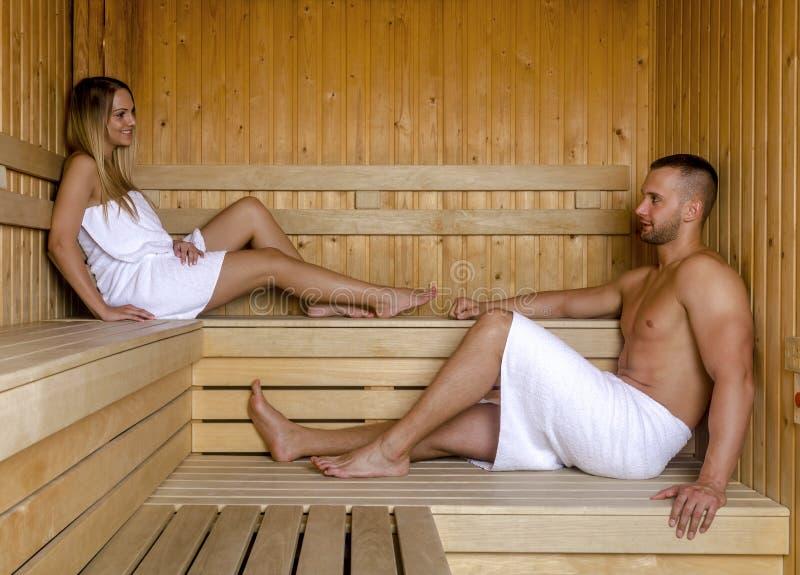 Привлекательный человек и красивая женщина ослабляя совместно в сауне стоковое фото rf