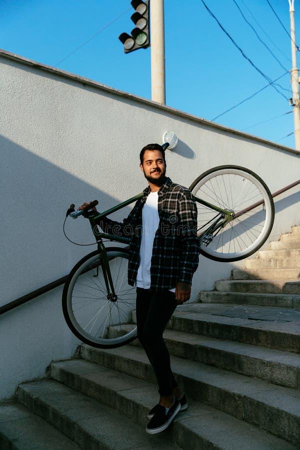 Привлекательный человек с велосипедом идя вниз на шаги в метро стоковое изображение