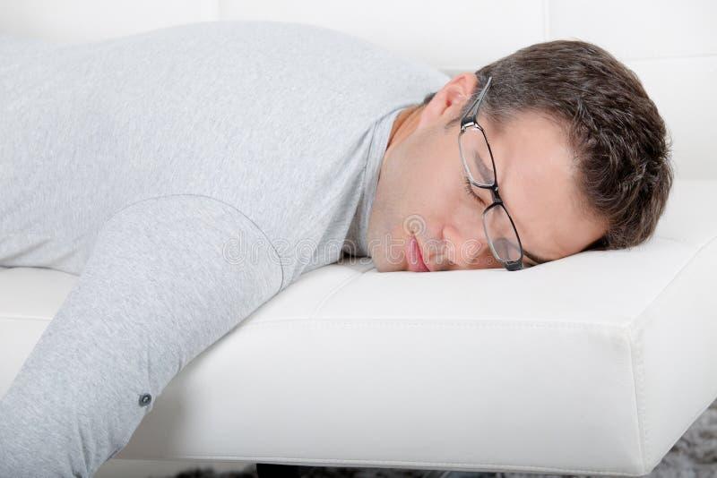 Привлекательный человек с стеклами napping на кресле стоковое изображение