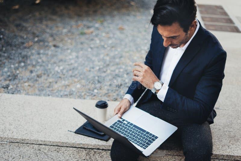 Привлекательный элегантный бизнесмен используя современную тетрадь и smartphone сидя снаружи запачканная предпосылка горизонтальн стоковые фотографии rf