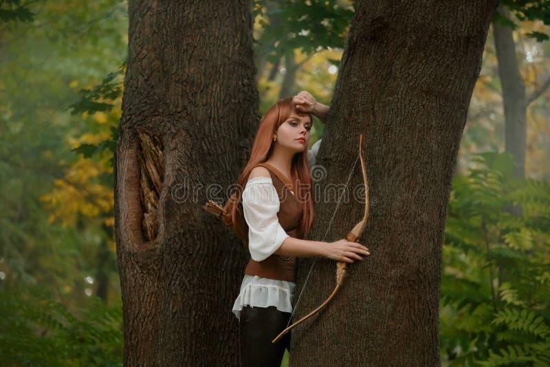 Привлекательный elven лучник не готовый для того чтобы снять жертву с деревянной стрелкой смычка, видом и сладкой девушкой с длин стоковая фотография