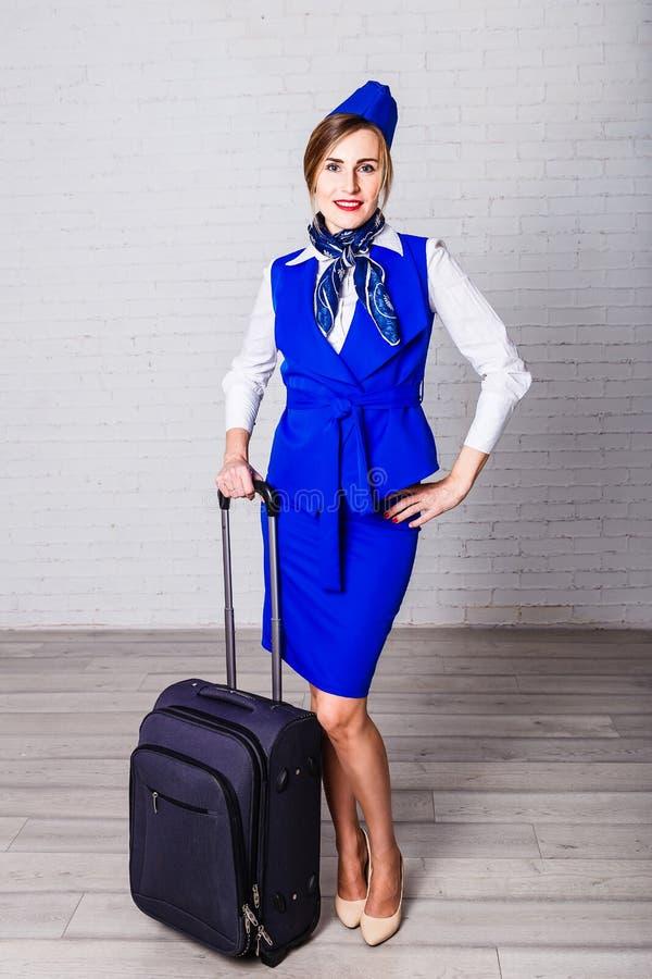 Привлекательный stewardess в голубых форме и крышке с чемоданом стоковое фото