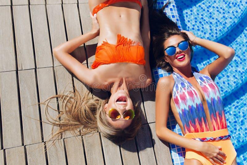2 привлекательных девушки блондинкы и брюнета с длинными волосами лежат на flor около бассейна Они носят бикини и купальник Они стоковые изображения rf