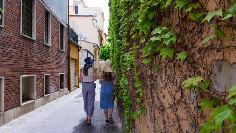 2 привлекательных женщины в panamas идя на переулок вдоль зеленой стены стоковая фотография