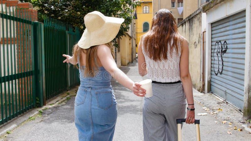 2 привлекательных женщины идя на переулки с чемоданами стоковое изображение