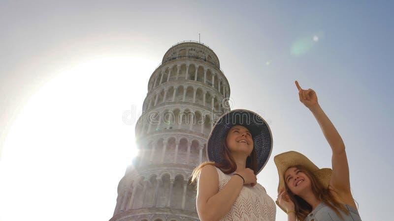 2 привлекательных женщины показывают друг к другу что-то под башней Пизы стоковая фотография