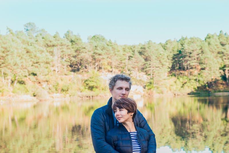 2 привлекательных мечтательных люд, пары в случайном обмундировании на диком лесе около воды Идилличная спокойная мирная свобода  стоковая фотография